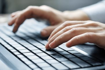 Image close-up of typing female hands on keyboard