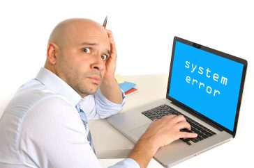 Image of worried young business man with technical problems at computer